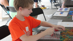 Youth participates in hands-on activity at STEM Day at the Fair