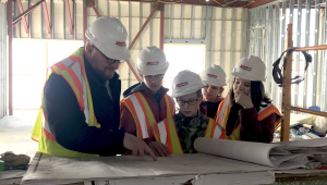 The 2018 STEM BEST partner Okoboji No Boundaries Leaving a Legacy team looks at blueprints of the new middle school.